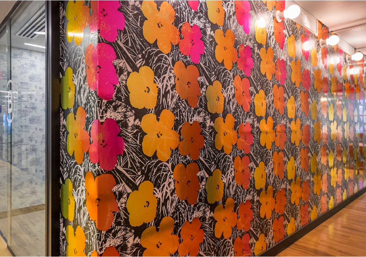 Warhol Flowers in Golden Shower brightens up any space including this hallway. You can see Brooklyn Toile in custom soft blue peeking out of the conference room as well.